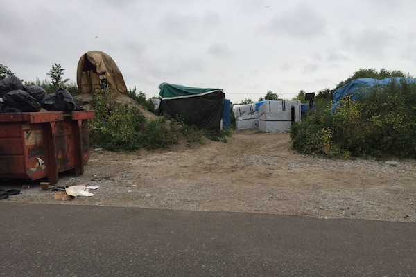 Calais Jungle Refugee Camp tents and shelters along a paved road